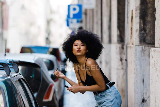 Retrato de una joven mujer étnica de pie cerca de la ventana del coche y haciendo maquillaje mientras se besa en la cámara en el fondo urbano - foto de stock
