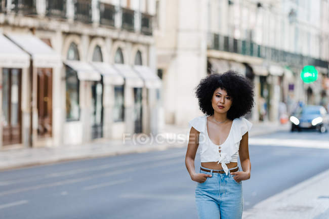 Ethnic woman in trendy outfit and looking at camera on summer day — Stock Photo