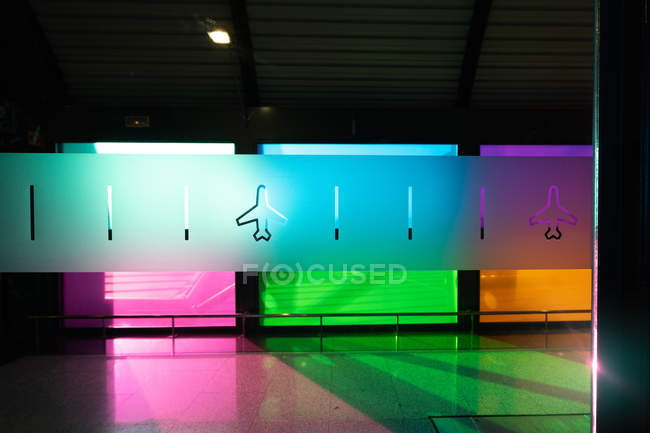 Plane icons decorating glass wall against colorful room of Madrid Barajas Airport in Spain — Stock Photo