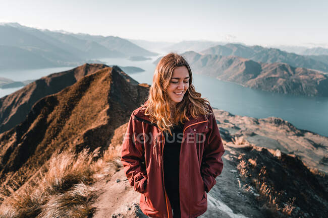 Smiling woman in coat standing on high peak of mountains in range smiling and looking down with closed eyes — Stock Photo