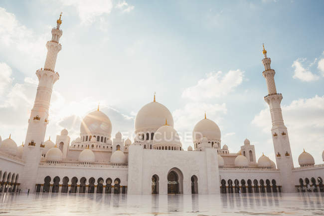 Exterior of white mosque with domes and minarets under bright blue sky, Dubai — Stock Photo