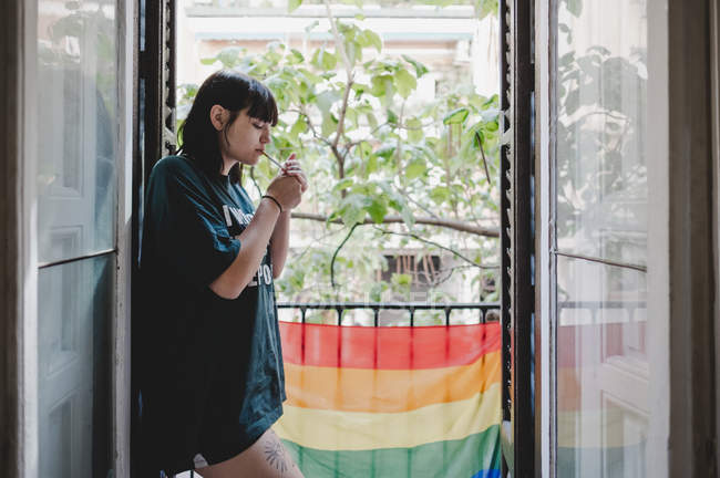 Side view of sensual young woman lighting cigarette while standing on balcony near LGBT flag — Stock Photo