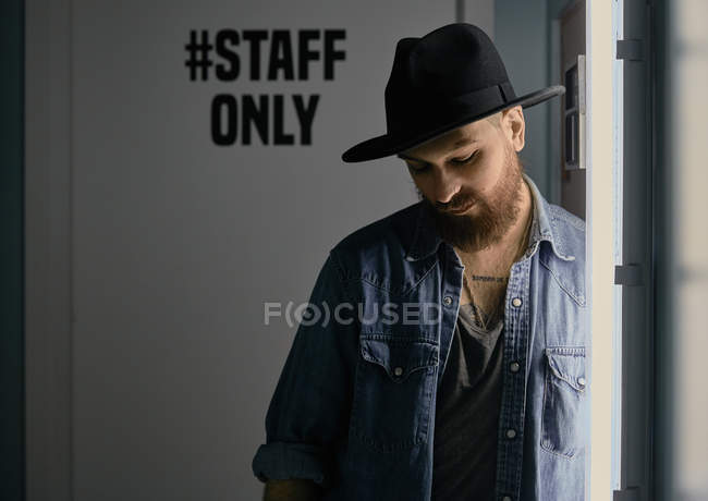 Young bearded handsome man in hat and denim shirt looking down in dark room — Stock Photo