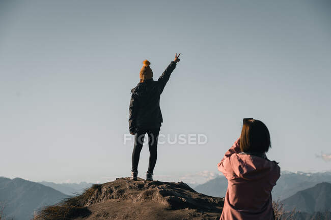 Back view of woman taking photo of girlfriend standing on rocky peak showing two fingers while traveling together — Stock Photo