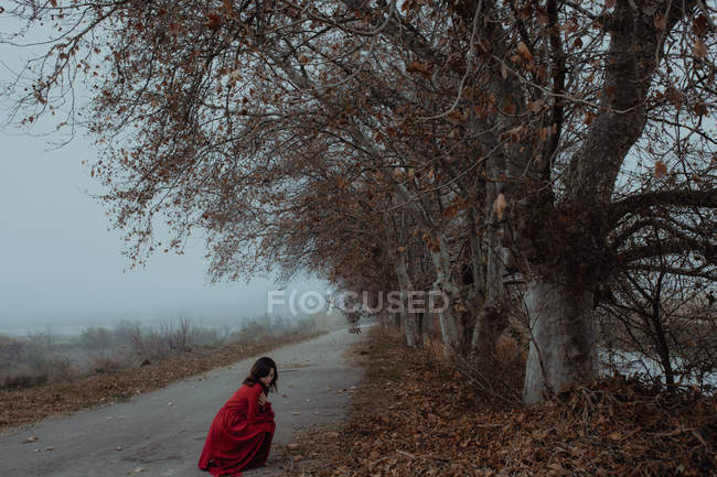 Dreamy woman in red dress on empty road of hazed mysterious terrain — Stock Photo