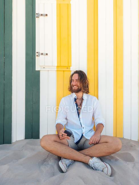 Hombre barbudo alegre en traje casual sosteniendo teléfono inteligente mientras está sentado en la arena contra la pared rayada en el resort - foto de stock