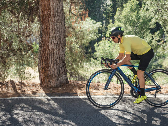 Healthy man riding bicycle on mountain road in sunny day — Stock Photo