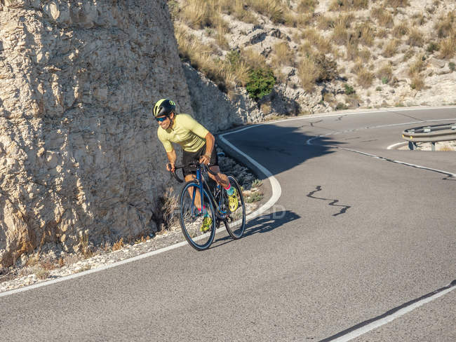 Здоровый человек езда на велосипеде по горной дороге в солнечный день — стоковое фото