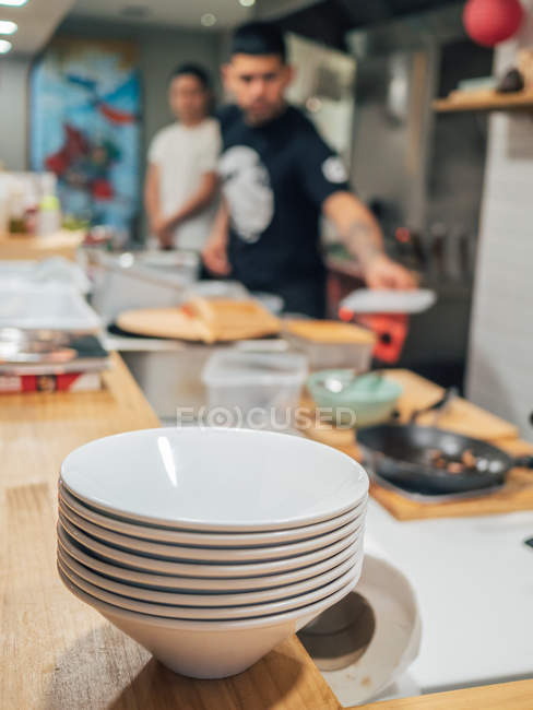 Стопка белых чаш, приготовленных для сервировки рамена на деревянном столе и размытой мужской кухни на кухне — стоковое фото