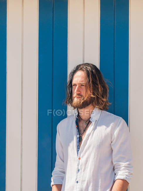 Confident bearded man in casual outfit posing against blue and white wall — Stock Photo
