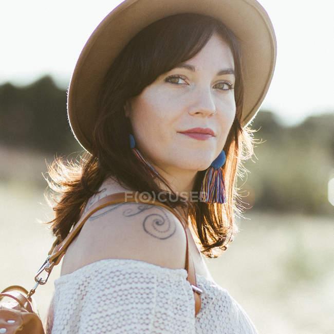 Портрет счастливой женщины в белой одежде и шляпе, стоящей на улице при дневном свете — стоковое фото