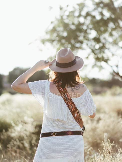 Frau in weißer Kleidung und Hut steht draußen im Tageslicht — Stockfoto
