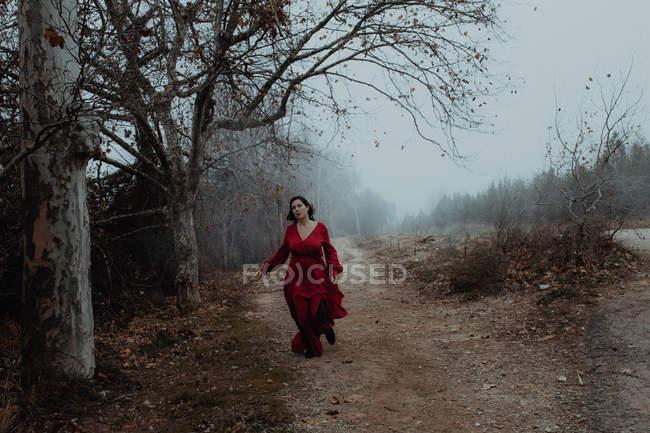 Verträumte Frau in rotem Kleid, die die leere Straße des verschwommenen, geheimnisvollen Geländes entlanggeht — Stockfoto