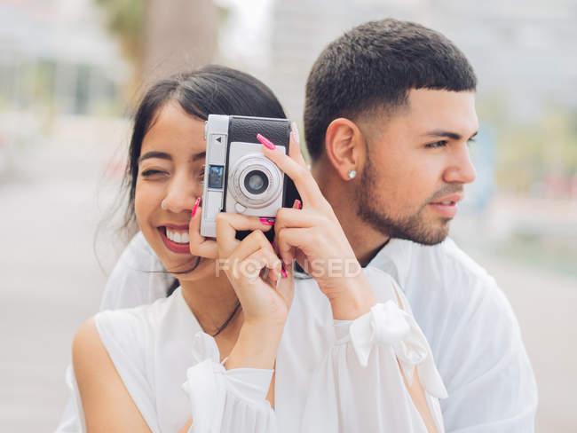 Молодая пара сидит и весело фотографирует на деревянной скамейке — стоковое фото
