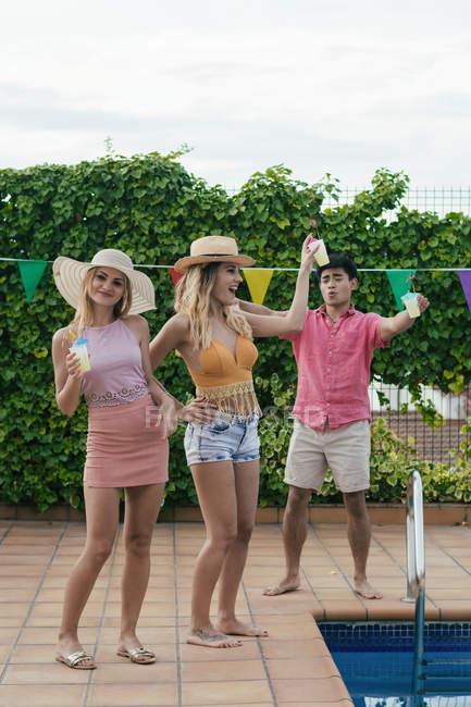 Gruppe von Freunden bei einer Poolparty, während sie tanzen, lachen und Cocktails trinken — Stockfoto