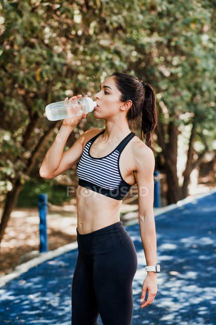 Femme en tenue de sport boire de l'eau de bouteille sur la piste de course le jour de l'été — Photo de stock