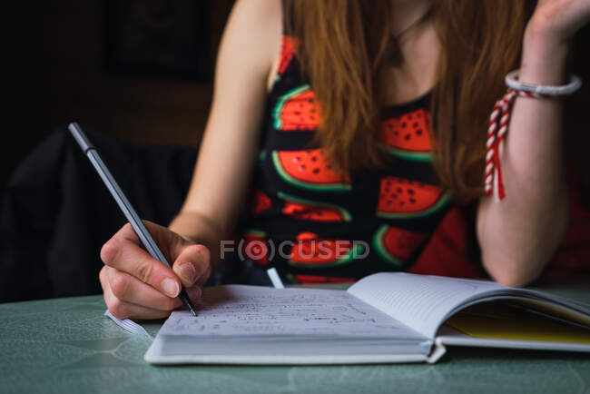 Unrecognizable crop woman sitting at table in cozy room and writing in notebook — Stock Photo
