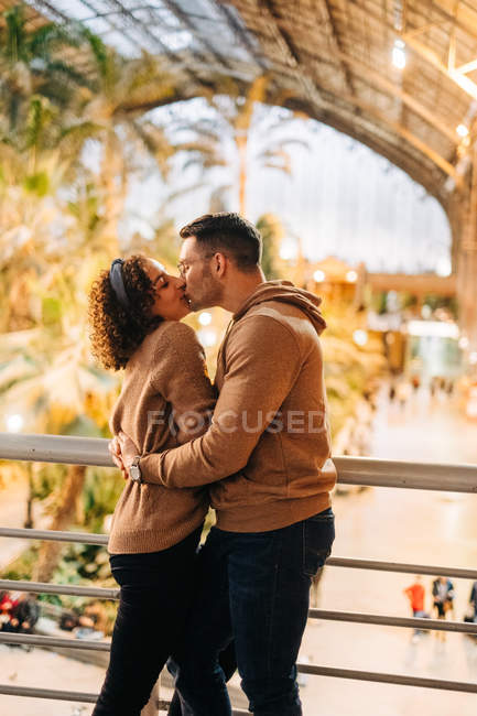 Jovem alegre e mulher abraçando e beijando enquanto está dentro do pavilhão iluminado durante a data — Fotografia de Stock