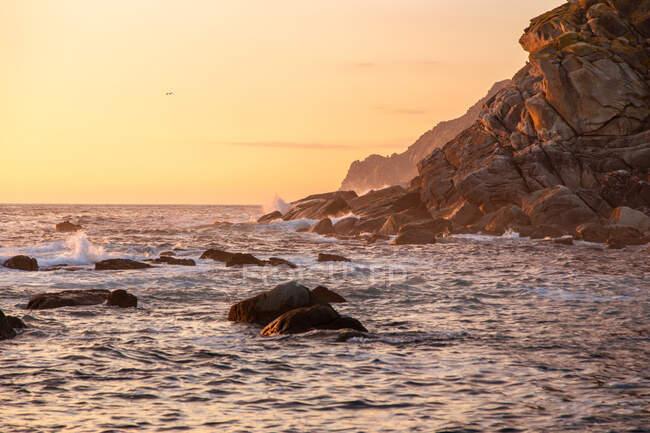 Vue sur le coucher de soleil orange et la mer calme sous un ciel sans nuages. — Photo de stock