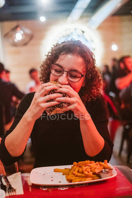 Hungry young woman biting tasty burger while sitting at table in brightly illuminated cafe — Stock Photo