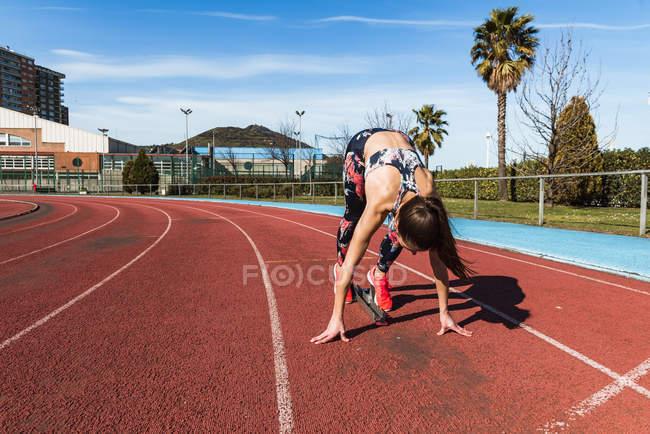 Стройная молодая женщина в спортивной одежде, устанавливающая ноги на стартовый блок и трогательная трасса перед забегом на стадион — стоковое фото