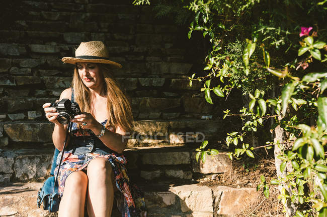 Traveling woman in dress and hat using camera while sitting on stone steps on sunny street — Stock Photo
