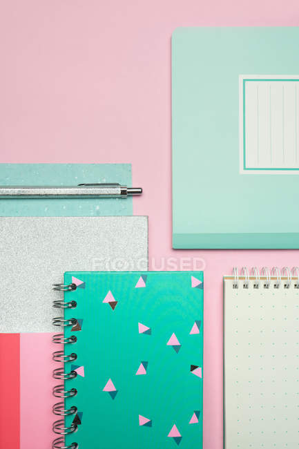Composition of colorful notebooks and pen arranged on pink desk — Stock Photo