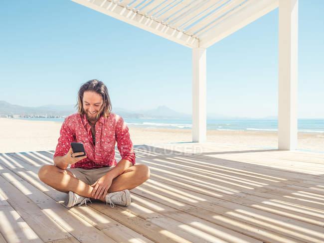 Homem barbudo navegando smartphone enquanto sentado no gazebo na praia de areia perto do mar no dia ensolarado — Fotografia de Stock