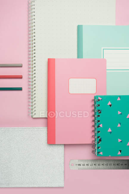Composition of colorful notebooks, ruler and pencils arranged on pink desk — Stock Photo