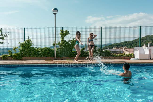 Amici che giocano con le pistole ad acqua in piscina in una soleggiata giornata estiva — Foto stock
