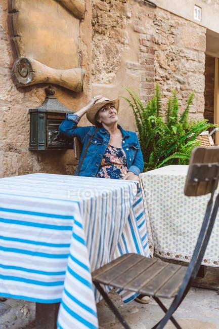 Mulher de chapéu de palha e vestido sentado no terraço do restaurante na cidade medieval — Fotografia de Stock