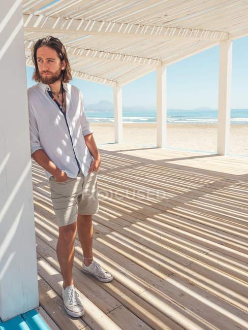 Красивый бородатый мужчина смотрит в сторону, опираясь на колонну белой беседки на песчаном пляже — стоковое фото