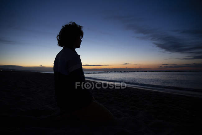 Silhouette of thoughtful man on seaside on background of sunset sea — Stock Photo