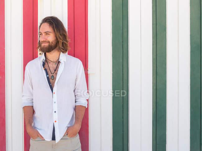 Улыбающийся бородатый мужчина в повседневной одежде, стоящий напротив полосатой стены на курорте — стоковое фото