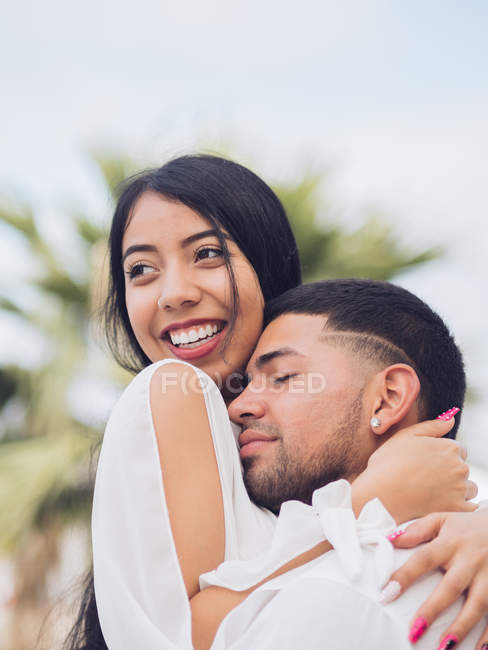 Молодий вродливий чоловік із заплющеними очима обіймає привабливу усміхнену жінку. — стокове фото