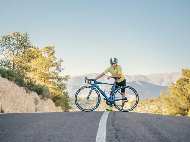 Здоровый человек отдыхает стоя с велосипедом на горной дороге в солнечный день — стоковое фото