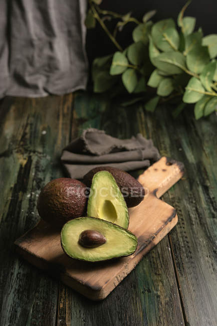 Whole and halved fresh avocados on rustic wooden table — Stock Photo