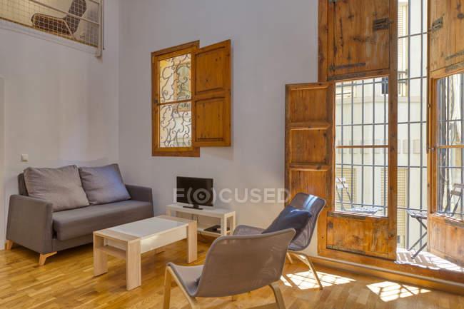 Interior da sala de visitas e das janelas à moda simples na luz do dia — Fotografia de Stock