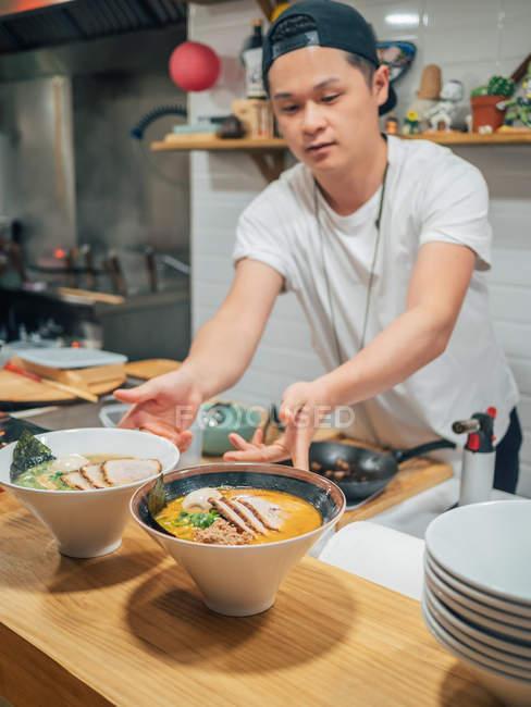 Молодой человек кладет миски свежеприготовленного традиционного японского блюда на деревянный прилавок в ресторане — стоковое фото