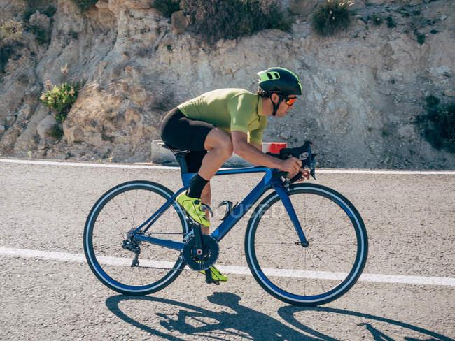 Крупный план здорового человека, катающегося на велосипеде по горной дороге в солнечный день — стоковое фото