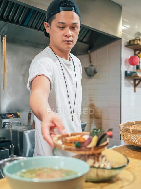 Multiracial человек приготовления японского блюда называется рамэн в азиатском ресторане в помещении — стоковое фото