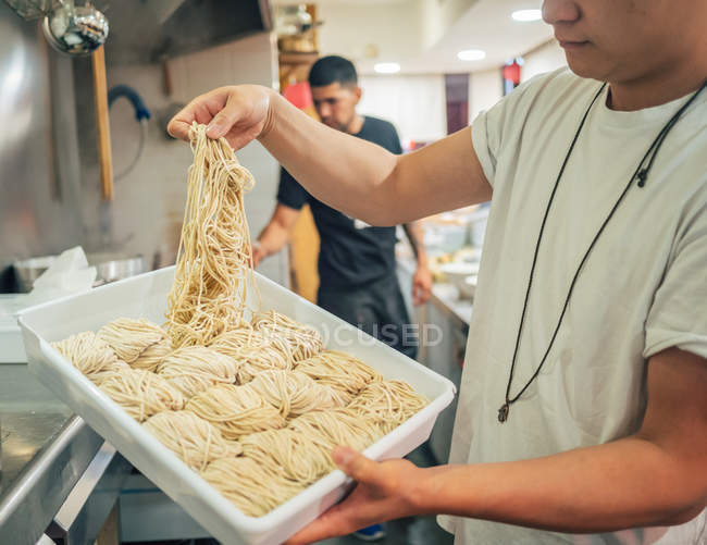 Side view of young multiracial men taking noodles from tray in restaurant — Stock Photo