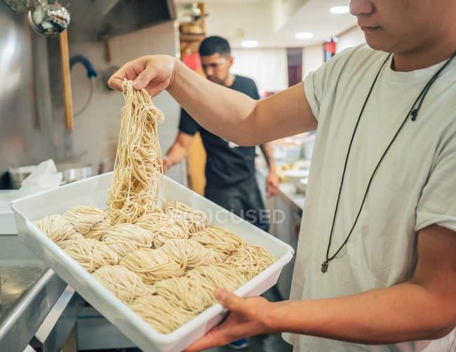 Vue de côté de jeunes hommes multiraciaux prenant des nouilles du plateau dans le restaurant — Photo de stock