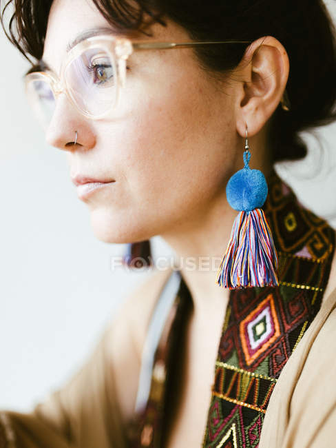 Side view of attractive dreamy young brunette with bright handmade earring of colorful threads — Stock Photo