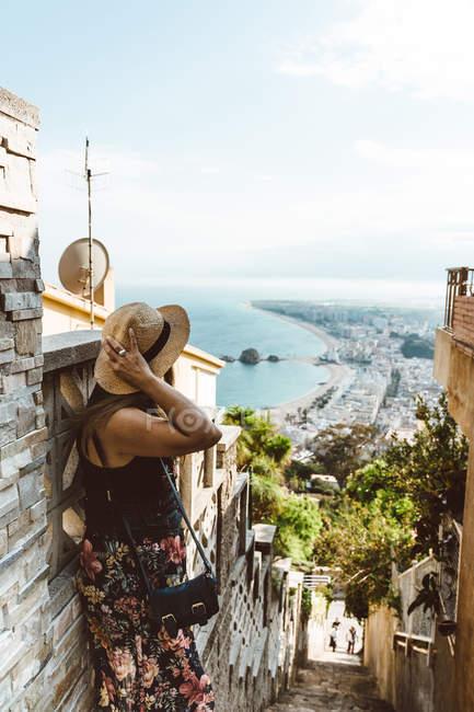 Donna irriconoscibile in abito estivo in piedi su scale di pietra di strada e guardando la costa del mare — Foto stock