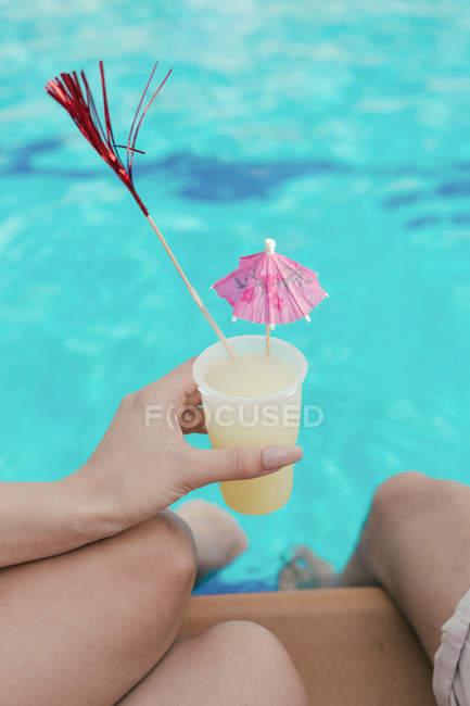 Група друзів влаштовує вечірку в басейні поки вони танцюють, сміються і п'ють коктейлі — стокове фото