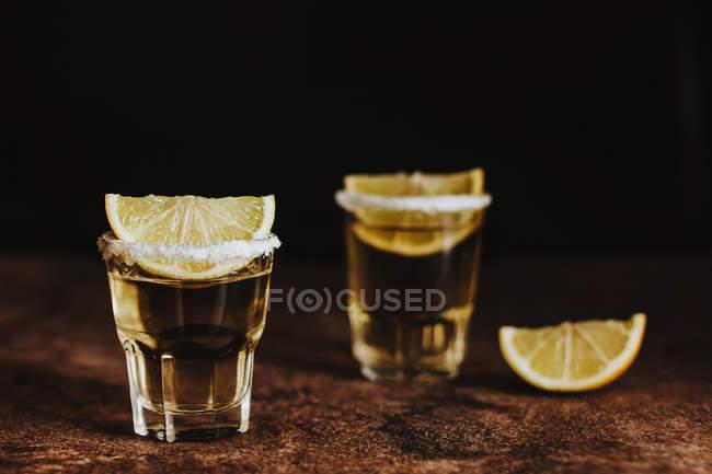 Традиционные текила выстрелы подается с кусочками свежей извести и соли на черной столешницы — стоковое фото