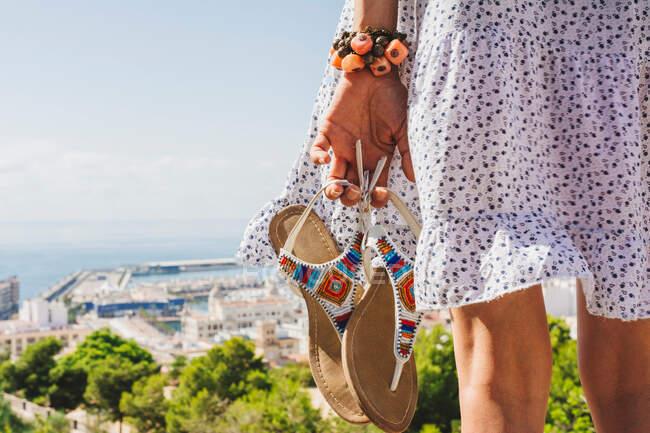 На задньому плані - молода жінка в літньому вбранні з барвистими сандалями в руці і чудовим браслет, який насолоджується чудовим краєвидом в яскравий день в Іспанії — стокове фото