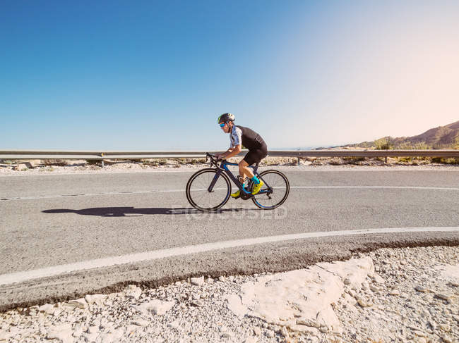 Healthy man riding bicycle on road in sunny day with barren landscape on background — Stock Photo
