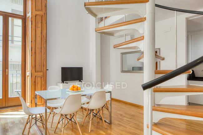 Інтер'єр простої стильною їдальні і сходи в сучасних дворівневих плоских у денному світлі — стокове фото
